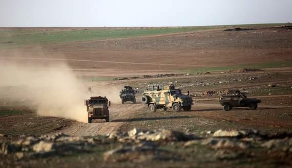 Подпись к изображению: Турецкий военный транспорт движется вблизи города Эль-Баб на севере Сирии