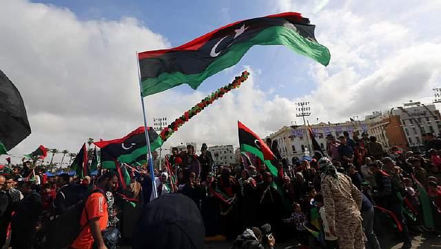 Подпись к изображению: Национальный флаг развевается над толпой в Триполи
