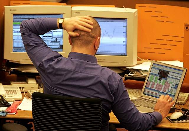 A Russian trader looks into computer screens during the session at MICEX stock exchange in Moscow, December 15, 2004. Once Russia's largest listed firm, YUKOS is now worth less than $2 billion, down from a peak of over $40 billion last year and its shares slumped another 12 percent before being suspended from trade by Moscow's MICEX exchange. REUTERS/Alexander Natruskin  AS/GB - RTRIA7B