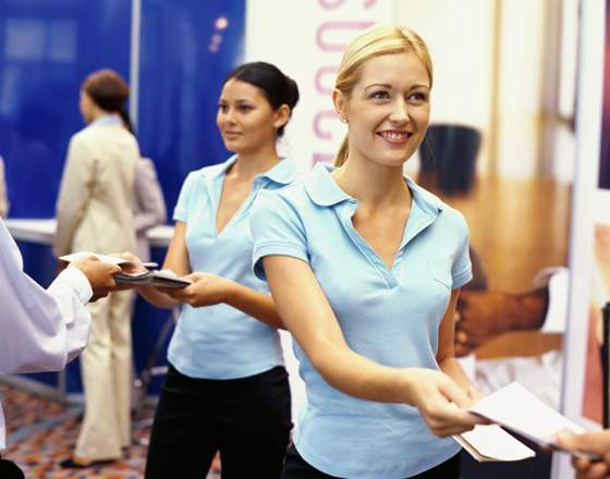 sales executives distributing brochures at an exhibition