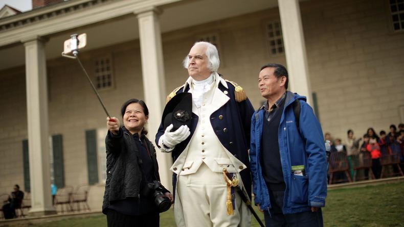 Туристы позируют с актером, изображающим Джорджа Вашингтона